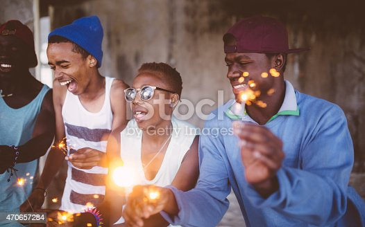 Group of celebratory African American teens happily dancing while holding sparklers