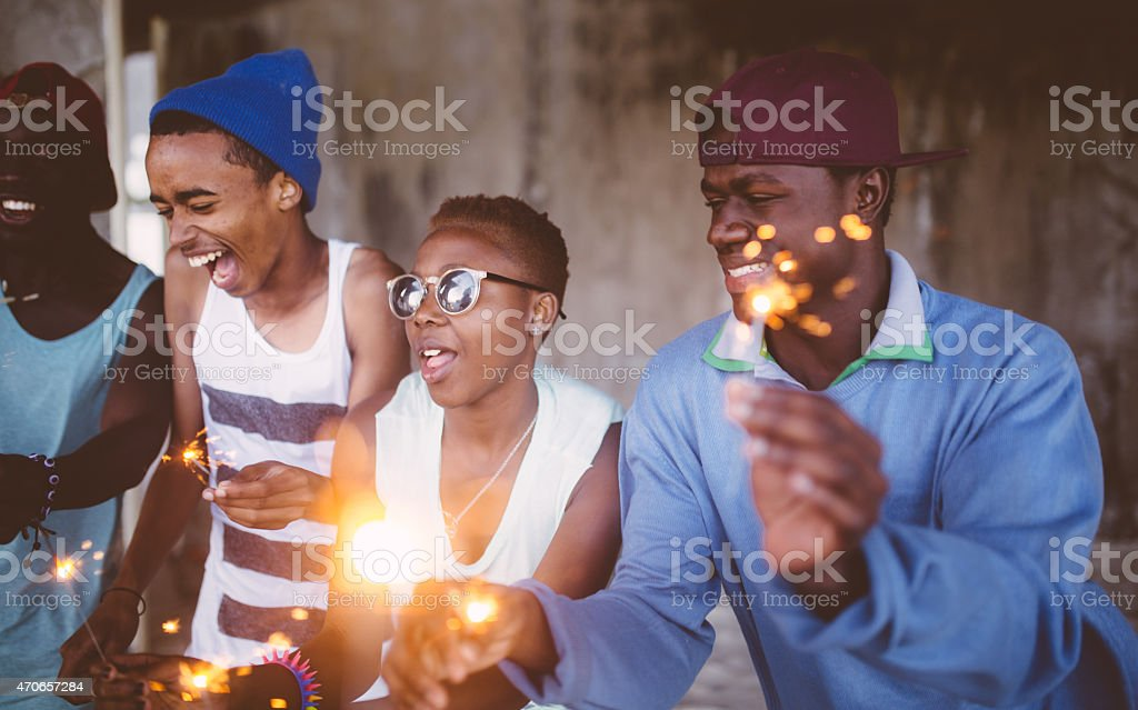 African American teens celebrating happily with sparklers stock photo