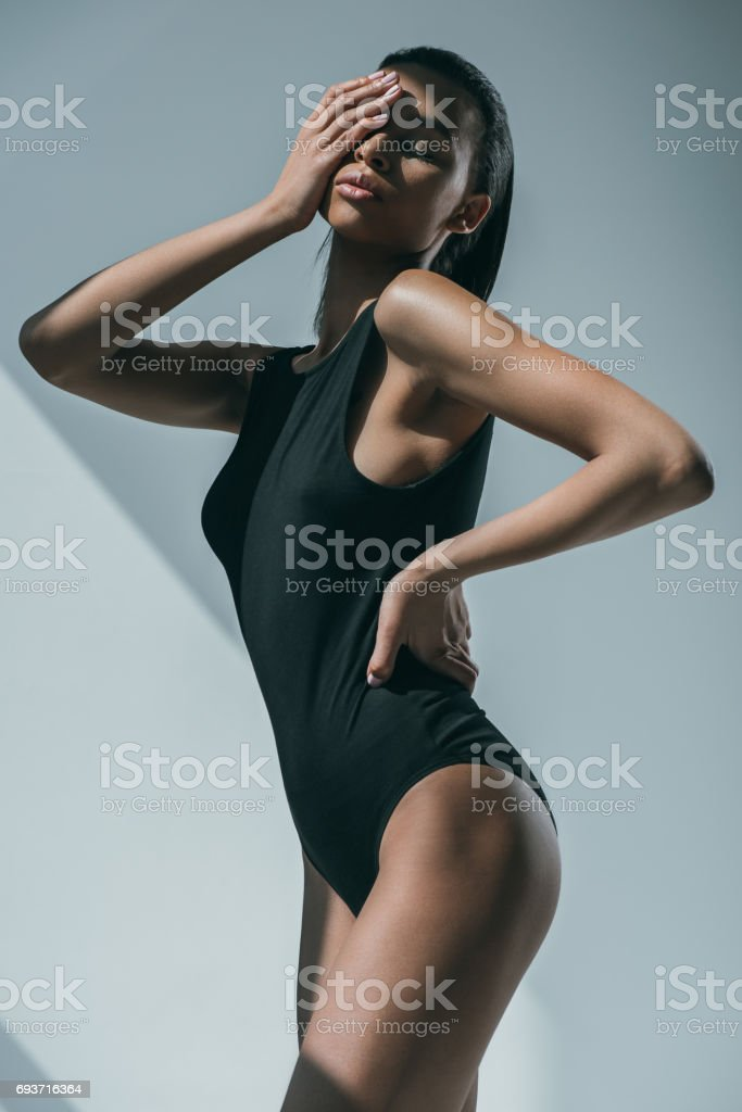 african american trendy woman with slim body touching her face and posing in black bodysuit stock photo