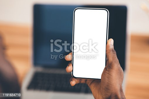 Useful App. Close-up of black man holding mobile phone with white blank screen. Mock up, rear view