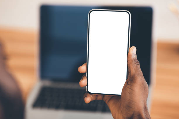 African american using black phone with blank screen Useful App. Close-up of black man holding mobile phone with white blank screen. Mock up, rear view close to stock pictures, royalty-free photos & images