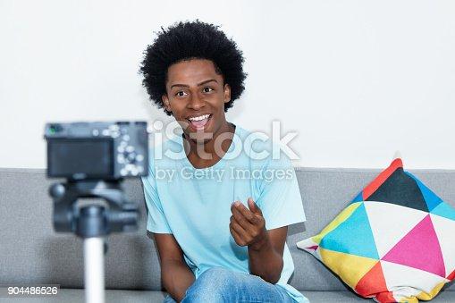 istock African american vlogger recording video blog 904486526