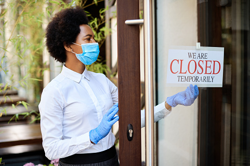 Black owner wearing protective face mask while hanging closed sign at entrance door of her cafe during COVID-19 epidemic.