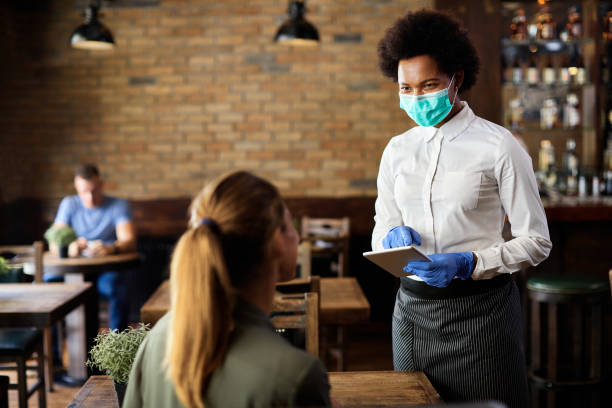 African American waitress with face mask and gloves using digital tablet while taking order from a gues stock photo