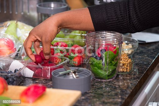 A portrait of an African American woman adding raspberries to ingredients whilst preparing a healthy drink/ smoothie.