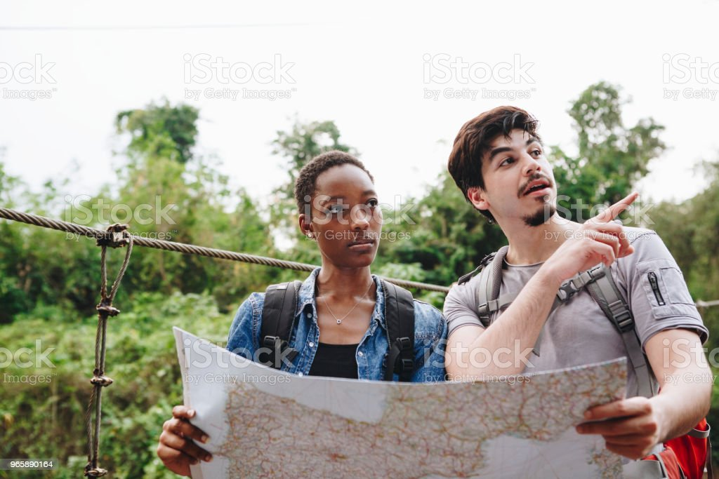 African American woman and a Caucasian man looking at a map together travel and teamwork concept - Royalty-free Adult Stock Photo