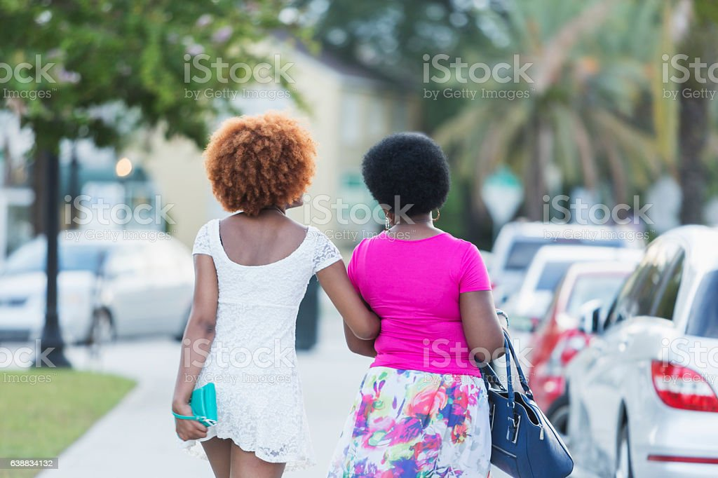 African American woman and adult daughter walking stock photo