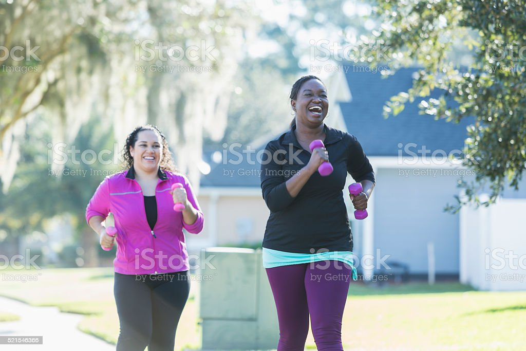 African American woman and friend running with dumbbells stock photo