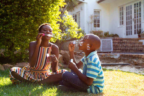 African American woman and her son, spending time together in the garden stock photo