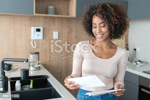 Portrait of an African American woman at home checking her mail and looking very happy - lifestyle concepts