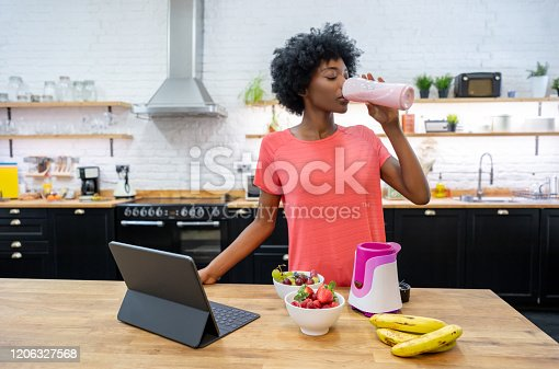 Portrait of a happy African American woman at home drinking a smoothie in the kitchen