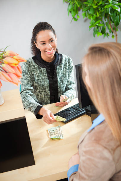 African American Woman Bank Teller Serving a Customer at Retail Bank Counter stock photo