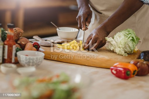 Cropped closeup of an African American woman standing at a counter in her kitchen at home cutting up vegetables for a delicious salad