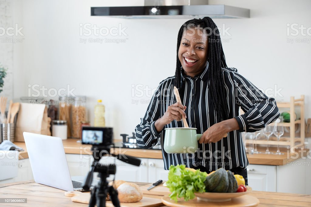 African american woman cooking vlogger recording video in kitchen at home Happy african american woman vlogger broadcasting live video online while cooking food in kitchen at home Adult Stock Photo