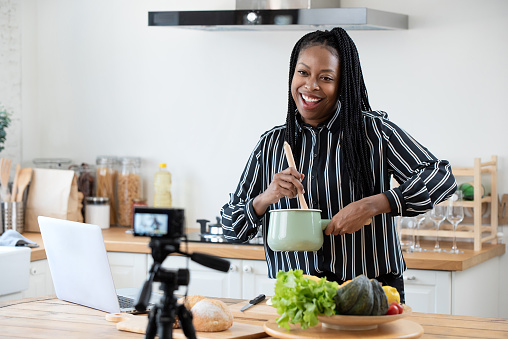 African American Woman Cooking Vlogger Recording Video In Kitchen At Home Stock Photo - Download Image Now