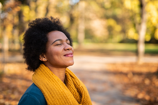 Happy mid adult African American woman enjoying a walk on autumn day in the park. Close up of tranquil woman inhaling and relaxing at the park.