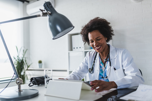 African American woman doctor working at her office doing telemedicine services. Helping patients online and by the phone. Primary care consultations