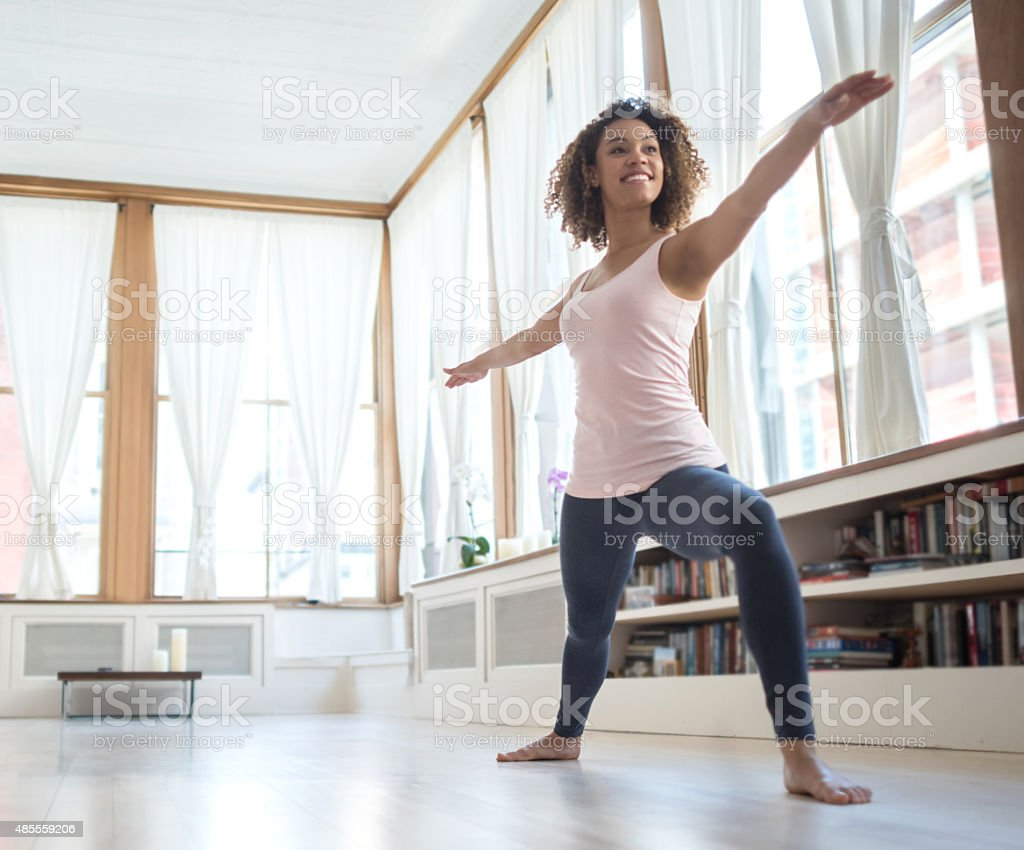 African American woman doing yoga at home stock photo