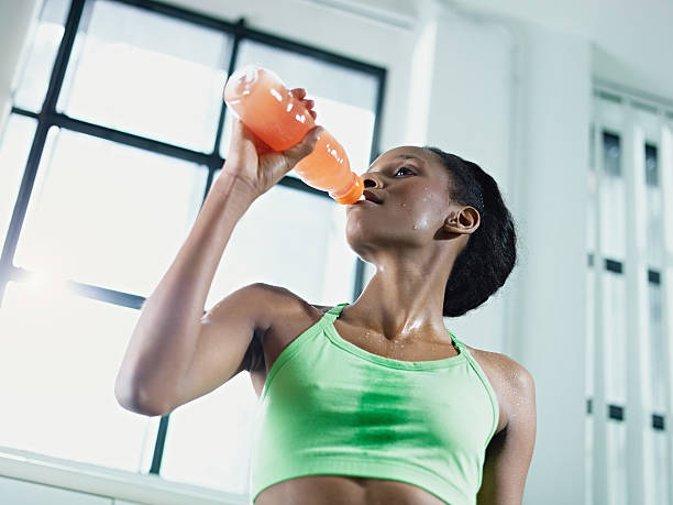 African American woman drinking an energy drink at the gym stock photo