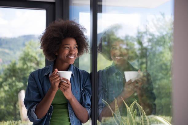 Afroamerikanische Frau trinkt Kaffee über das große Fenster – Foto