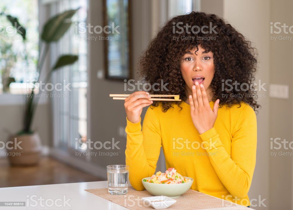 African american woman eating asian rice at home cover mouth with...