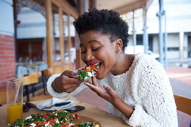 afro-americana donna mangiando pizza al ristorante all'aperto - cucina vegetariana foto e immagini stock