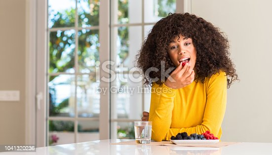 African american woman eating raspberries and blueberries at home with a confident expression on smart face thinking serious