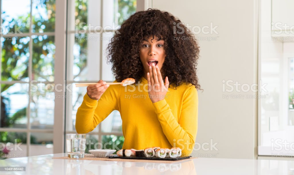 African american woman eating sushi using chopsticks at home cover...