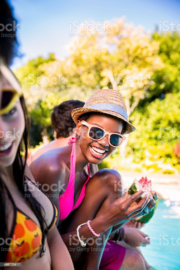African american woman enjoying watermelon with friends stock photo