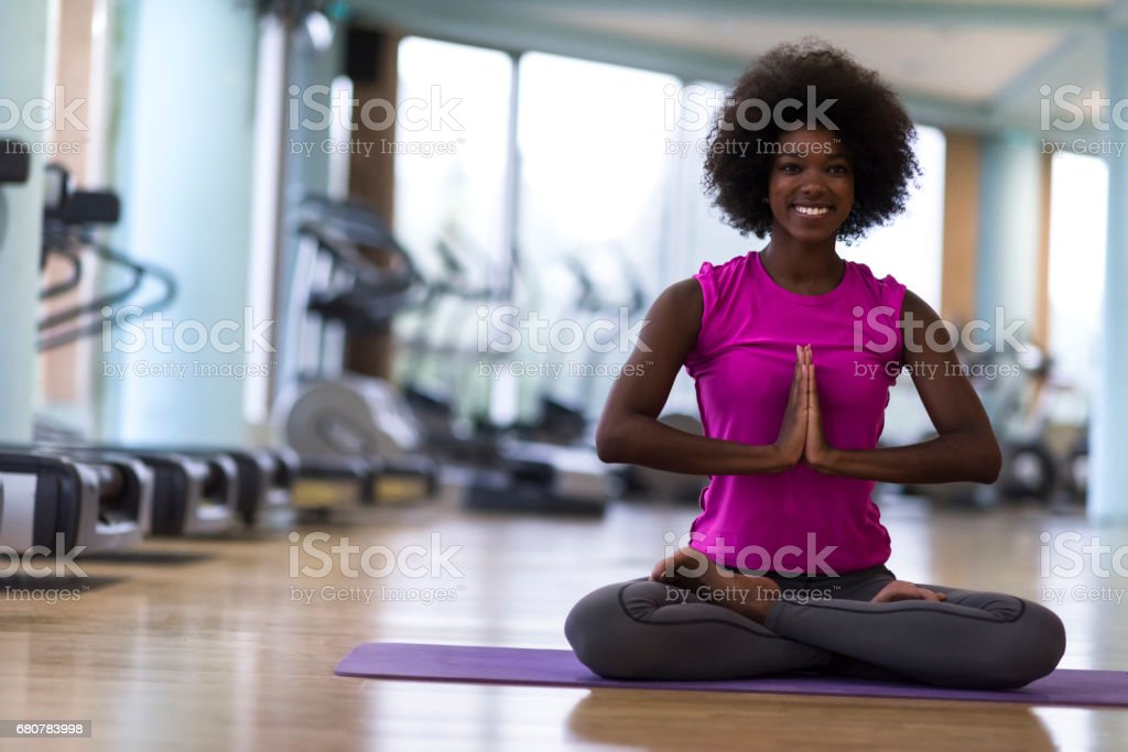 african american woman exercise yoga in gym stock photo