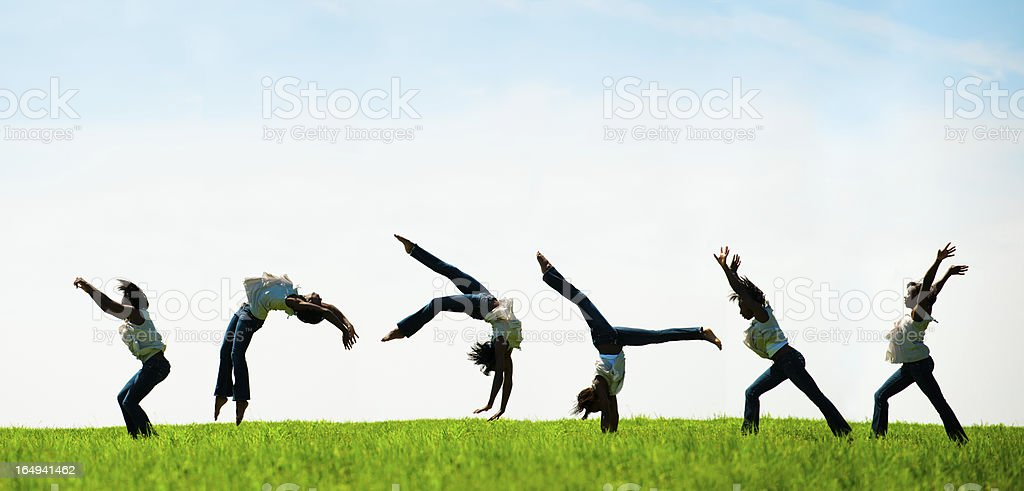 African American Woman Flips through Scenic Field (silhouette) stock photo