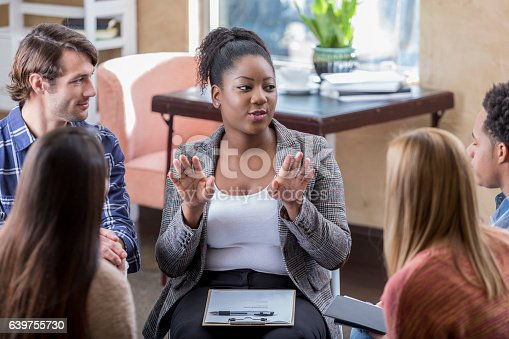 istock African American woman gestures during meeting with colleagues 639755730