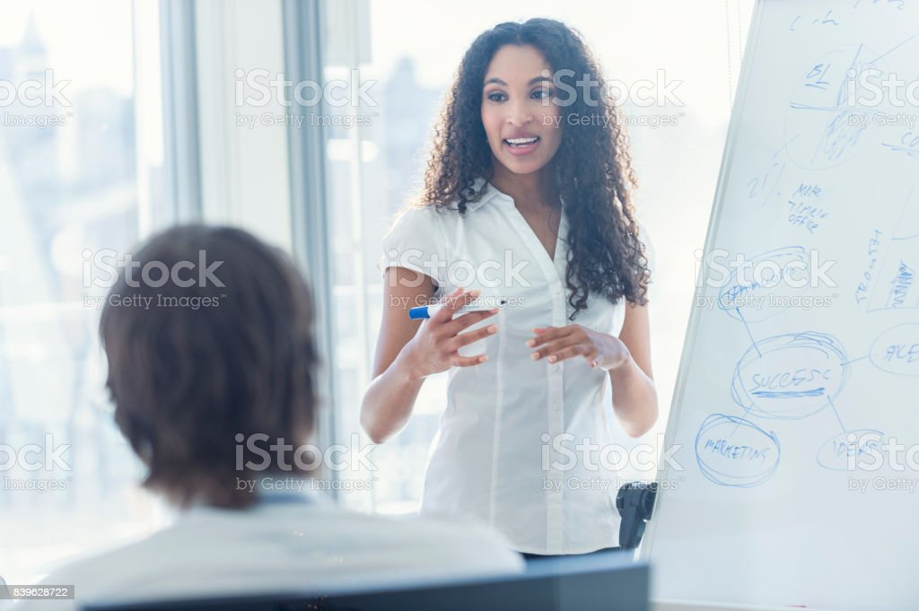 African American woman giving a presentation to her team. stock photo