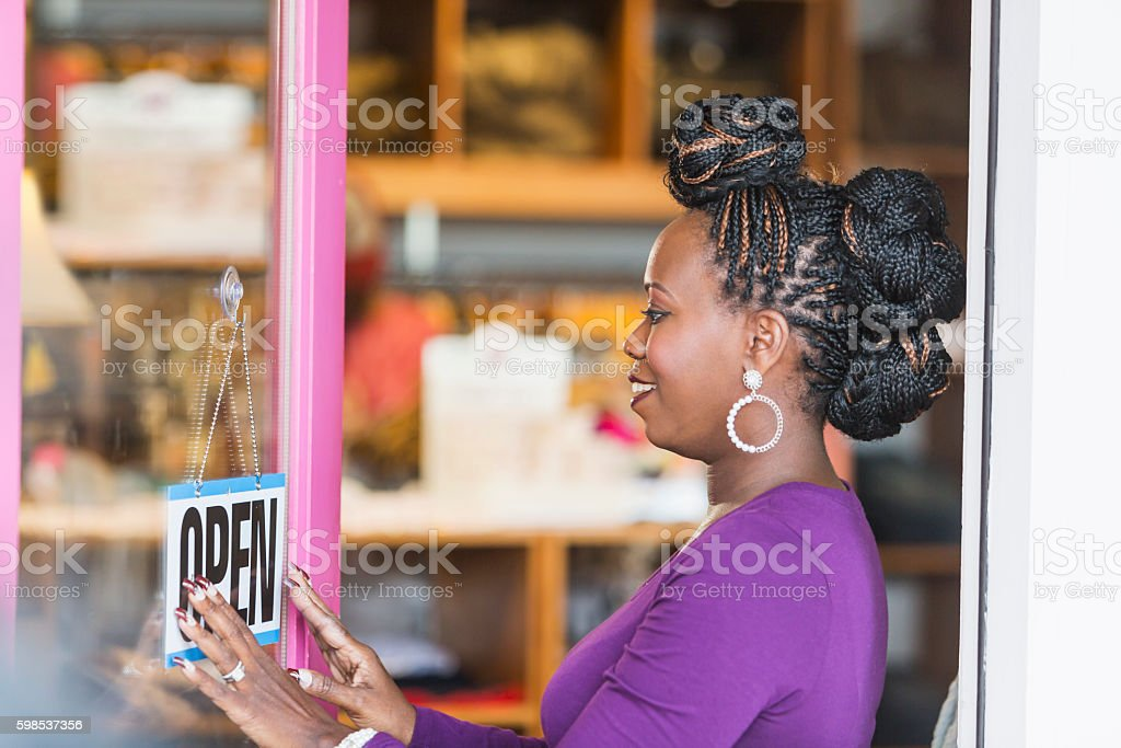 African American woman hanging OPEN sign on store door photo libre de droits