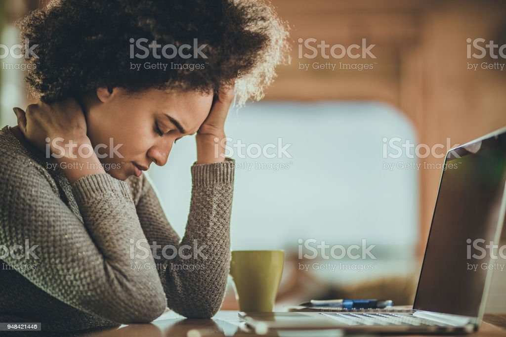 African American woman having a headache from working on a computer at home. stock photo