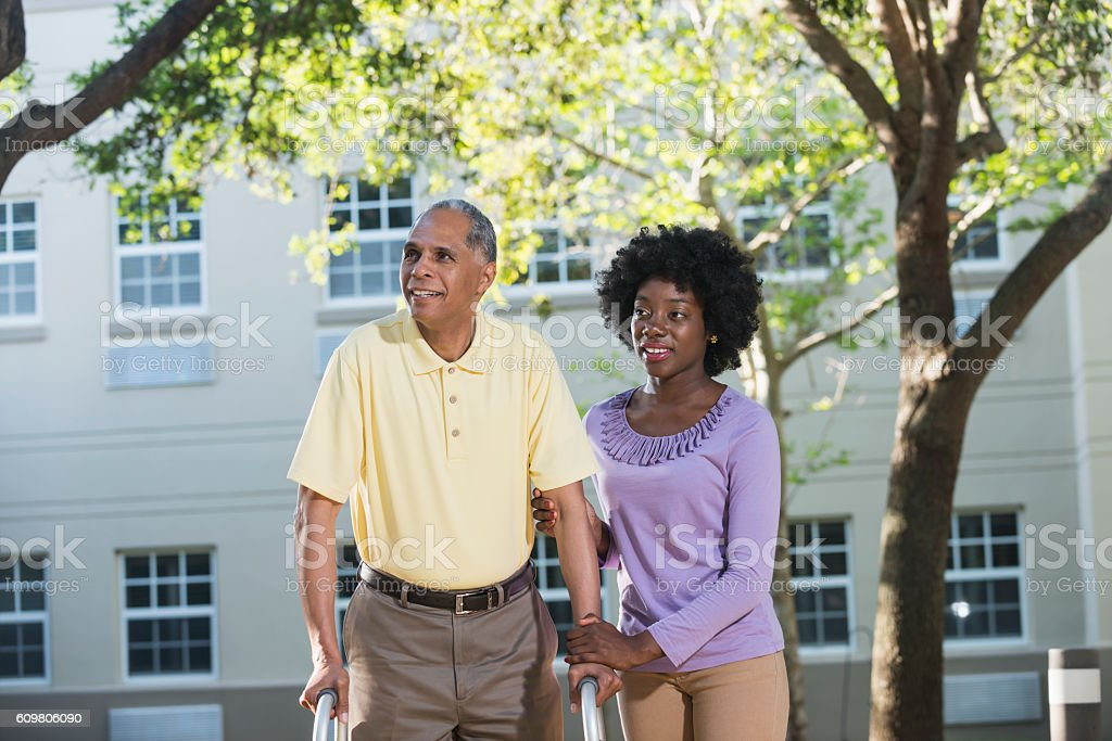 African American woman helping her father with walker stock photo