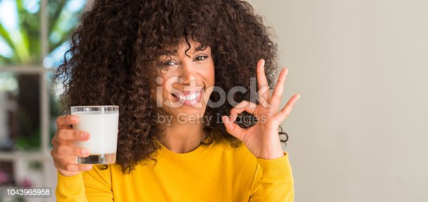 African american woman holding a glass of milk doing ok sign with fingers, excellent symbol