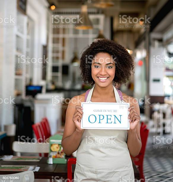 African american woman holding an open sign at a restaurant picture id504753080?b=1&k=6&m=504753080&s=612x612&h=dfkf7yaqaad3egcsk8zirm nlspx1bq5rsqgf4uhqzc=