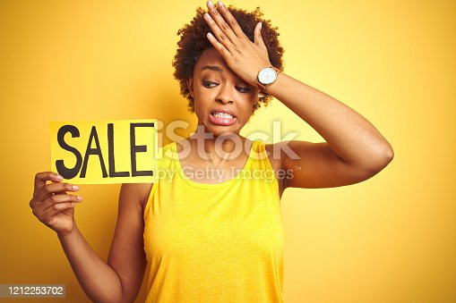 istock African american woman holding sale board over yellow isolated background stressed with hand on head, shocked with shame and surprise face, angry and frustrated. Fear and upset for mistake. 1212253702