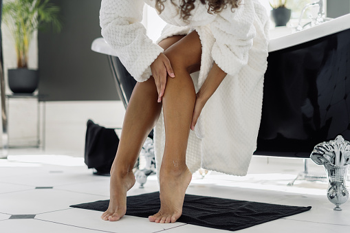 Concept of cosmetology and dermatology. Cropped view of african american woman in bathrobe touching soft legs after epilation and depilation procedure, spending morning in bathroom