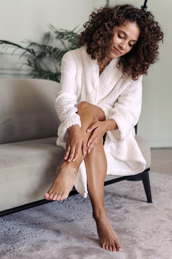 Skincare and body care concept. Vertical view of calm african american woman in bathrobe sitting at home, touching soft skin on legs after shaving and waxing hair removal procedure, smiling nice
