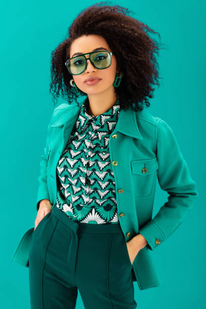 african american woman in jacket with hands in pockets looking at camera isolated on turquoise stock photo