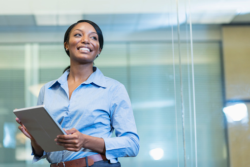 istock African American woman in office holding digital tablet 639866074