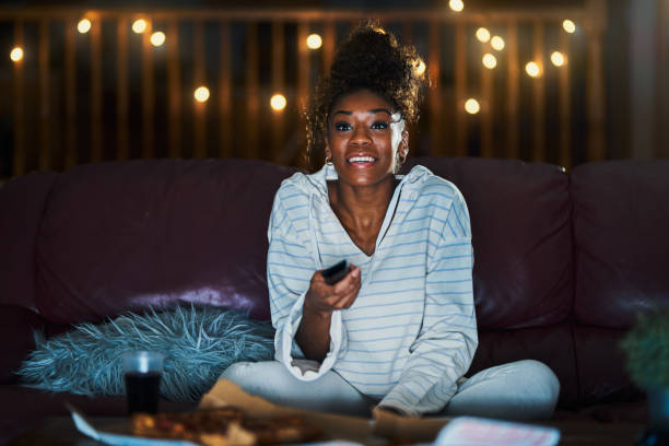 african american woman in pajamas staying up late at night eating pizza stock photo