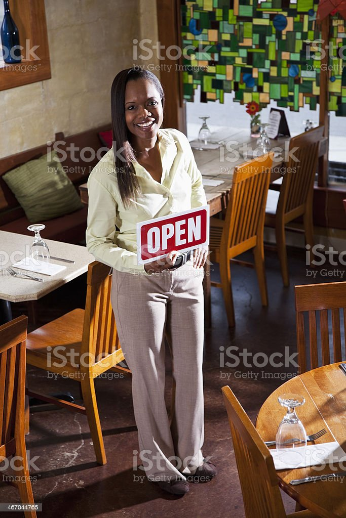 African American woman in restaurant open for business stock photo
