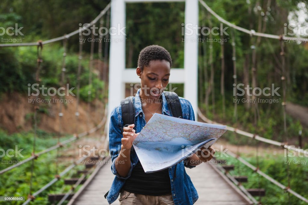 African American woman looking at a map travel and explore concept stock photo
