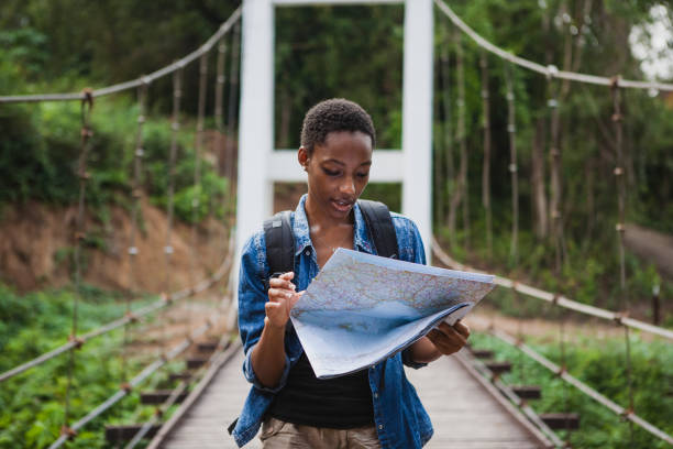 afrikaanse amerikaanse vrouw op zoek naar een kaart reizen en verkennen concept - toerist stockfoto's en -beelden