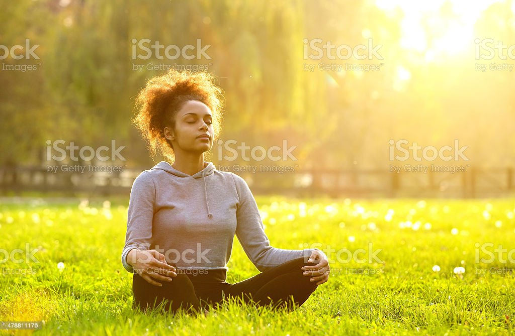 African american woman meditating in nature stock photo
