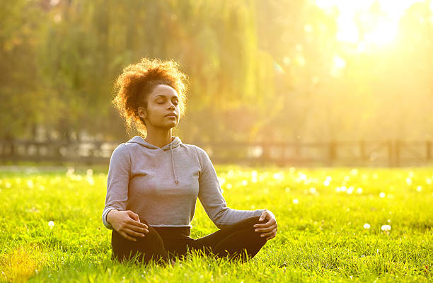African american woman meditating in nature Young african american woman meditating in nature eyes closed woman stock pictures, royalty-free photos & images