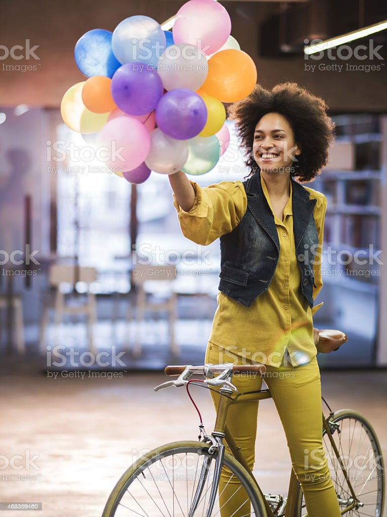 African American woman on a bike holding colorful balloons. royalty-free stock photo
